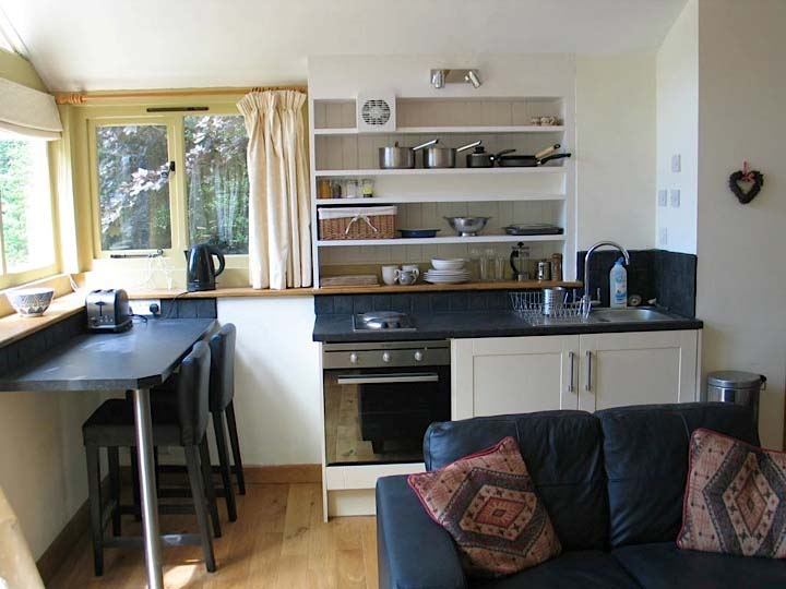 Nuthatch Cottage: interior, showing the kitchen area, the breakfast bar and the sofa